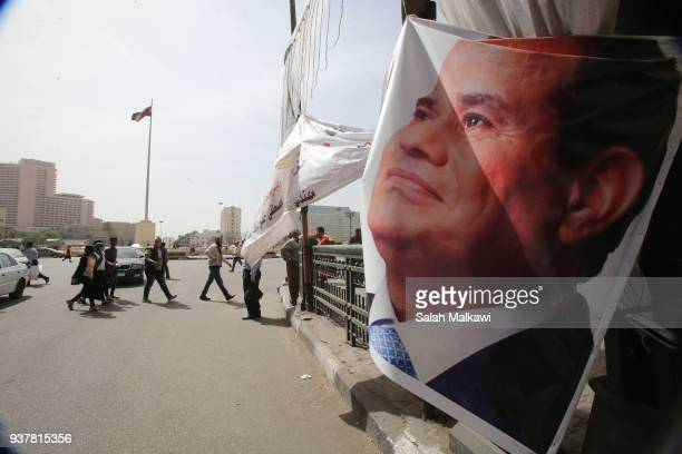 People in the street near a campaign poster for Egyptian President Abdel Fattah alSisi one day before the presidential elections on March 25 2018 in...