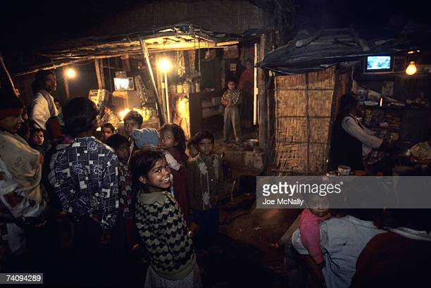 People in the streets gather around shops with televisions at night in January of 1999 in the slums of New Delhi India The Indus Valley civilization...