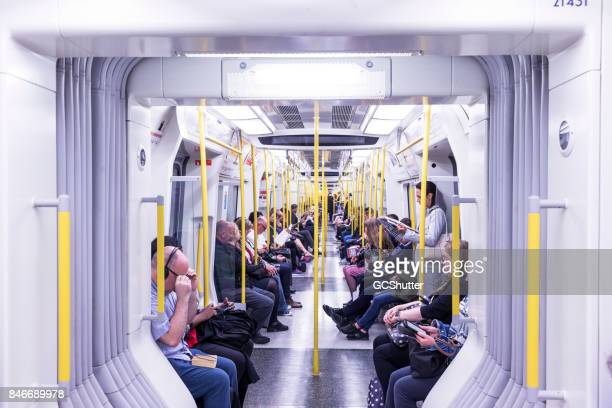 people in the tube patiently waiting for their stop. - metropolitana di londra foto e immagini stock