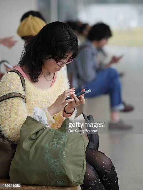 People in the waiting room of the 21st Century Museum of Contemporary Art, Kanazawa using their smartphones.