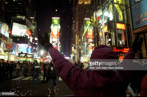 People in Times Square enjoy the confetti as it falls around them while they wait for the countdown to the new millennium.