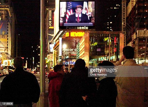 People in Times Square watch Vice President Al Gore concede the race for president to George W. Bush December 13, 2000 on a giant video screen in New...
