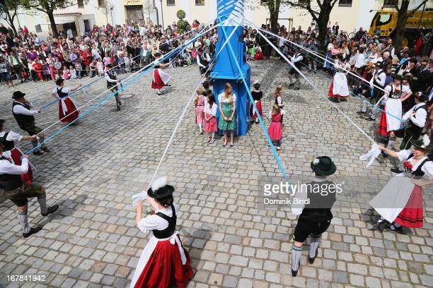 People in traditional Bavarian costumes perform a traditional dance during the traditional Bavarian maypole raising in Ismaning on May 1 2013 in...