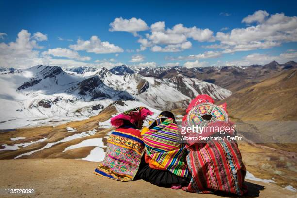people in traditional clothing against snowcapped mountains - perù foto e immagini stock