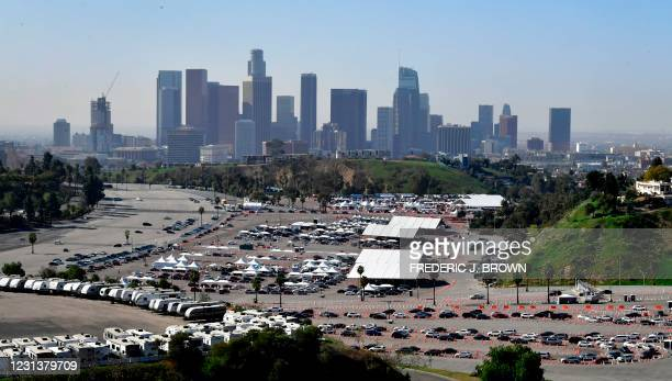 People in vehicles arrive and wait in line for their Covid-19 vaccinations in the parking lot at Dodger Stadium in Los Angeles, California on...