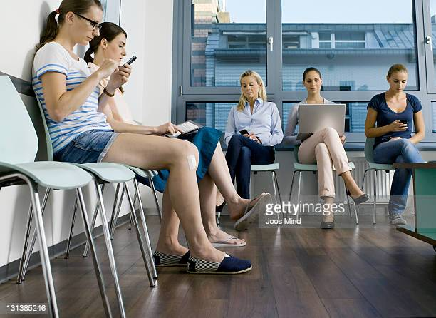 people in waiting room using digital equipment - doctor's surgery stock pictures, royalty-free photos & images
