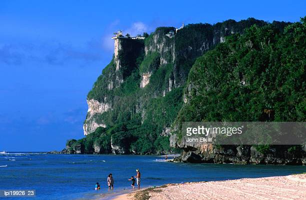 people in water at tumon beach with amantes (two lovers) point behind, tumon, guam - guam stock pictures, royalty-free photos & images