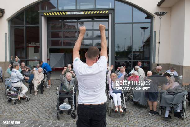 People in wheelchairs affected by an evacuation due to a bomb disposal do their morning exercises in front of an emergency shelter in Dresden eastern...