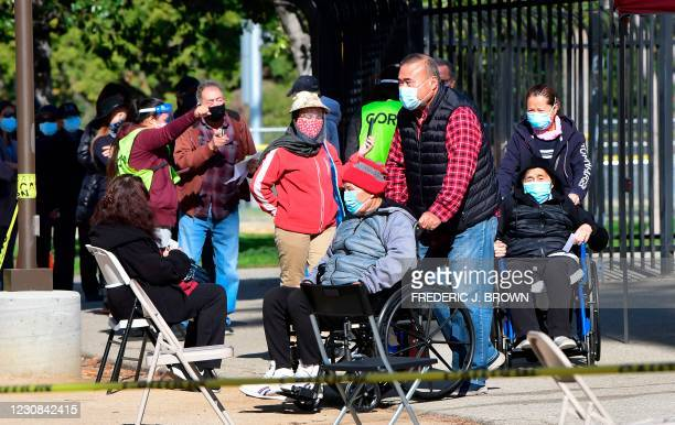 People in wheelchairs are directed by a volunteer to a waiting area after getting a Covid-19 vaccine at Lincoln Park in Los Angeles, California on...