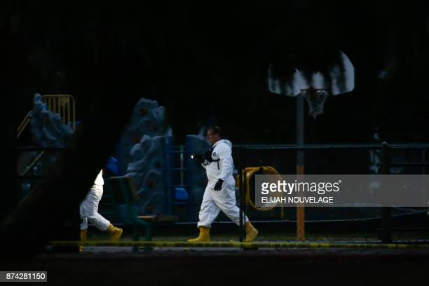People in white protective suits are seen on the Rancho Tehama Elementary school grounds after a shooting on November 14 in Rancho Tehama California...