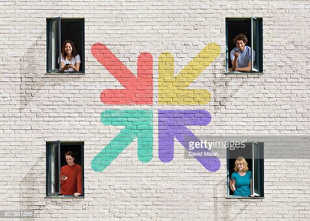 People in windows in a wall