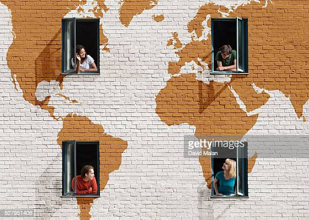 People in windows in a wall with painted map