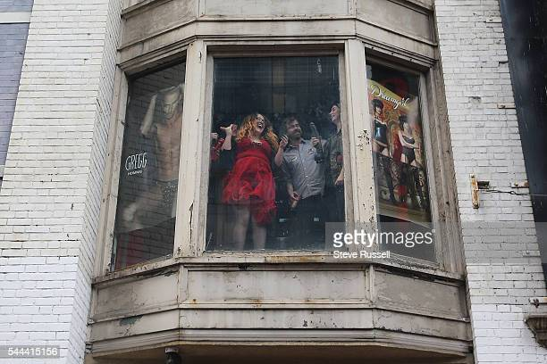 TORONTO ON JULY 3 People in windows react to seeing the Prime Minister while holding dildos during the the 2016 Toronto Pride parade along Yonge...