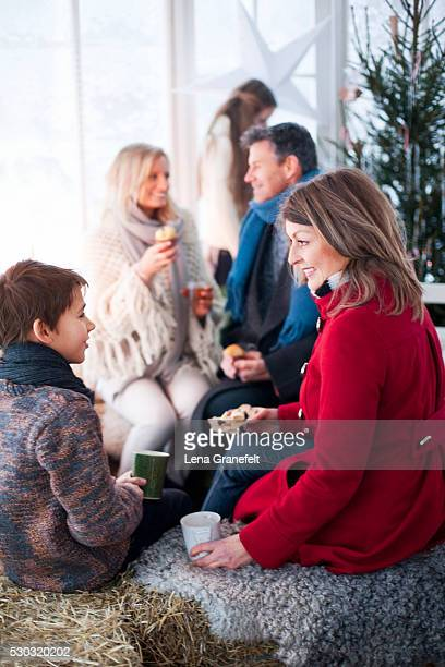 People in winter coats at Christmas party in greenhouse