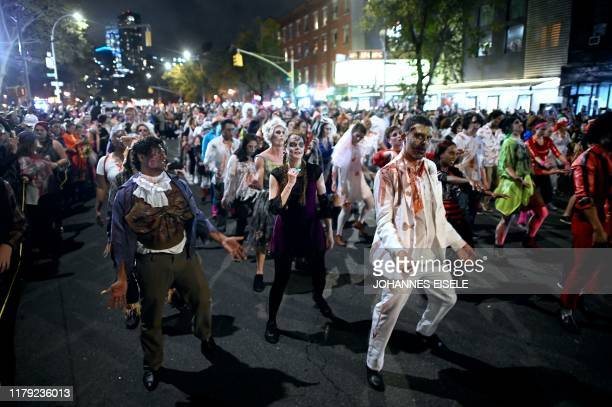 People in zombie costumes participate in the annual Village Halloween parade on Sixth Avenue on October 31 2019 in New York