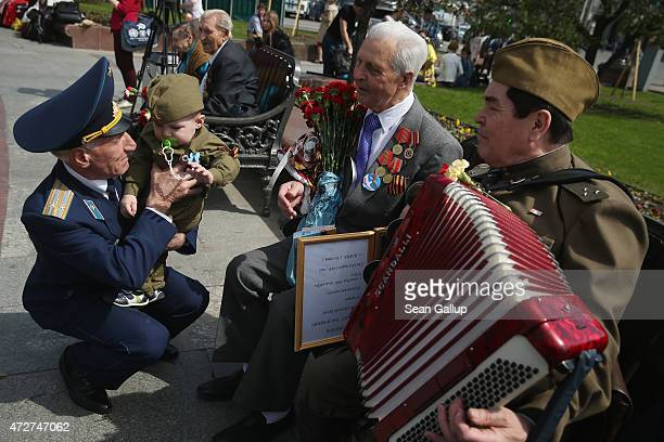 People including a veteran of World War II gather near the Bolshoi Theater to celebrate Victory Day as part of celebrations marking the 70th...