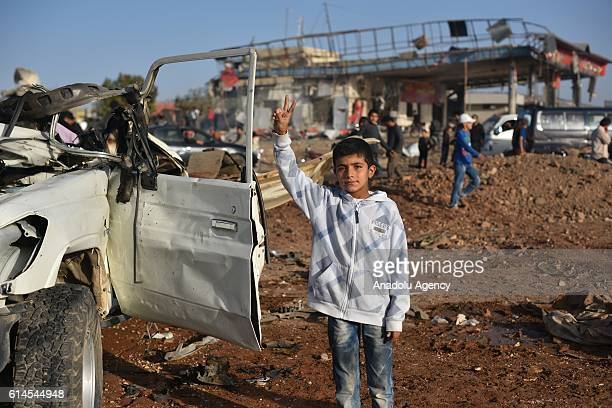 People including children inspect the wreckage at the site of the car bomb attack killing 19 people in Azaz town of Aleppo Syria on October 14 2016