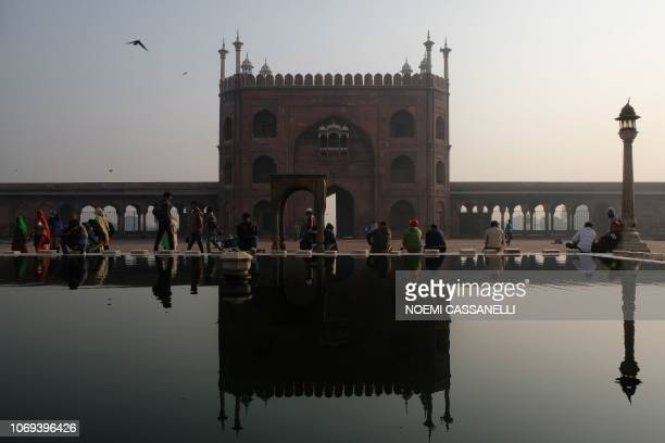 People including Indian Muslims sit and walk by the ablution pool at Jama Masjid in the old quarters of New Delhi on December 7, 2018. - The mosque,...