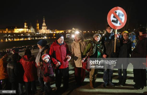 People including one man holding a sign of a markedthrough swastika form a human chain in the city center as a statement against neoNazis on the 69th...
