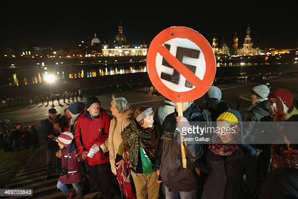 People, including one man holding a sign of a marked-through swastika, form a human chain in the city center as a statement against neo-Nazis on the...