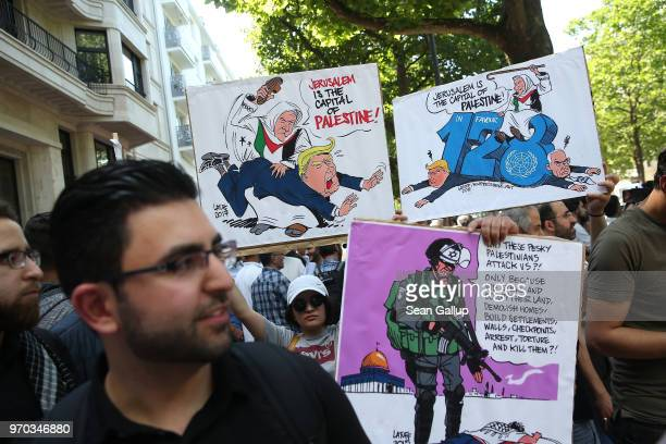 People including one person holding a protest sign that shows US President Donald Trump being spanked by an elderly man wearing a Palestinian flag...