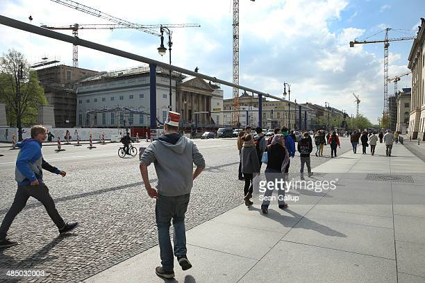 People including one young man wearing a large paper cup as a hat walk down Unter den Linden avenue near the Neue Wache war memorial on April 8 2014...