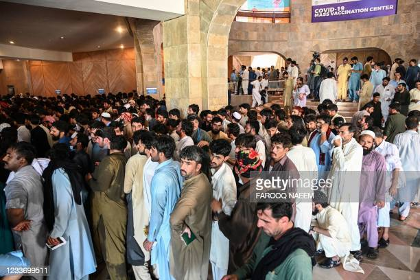People including overseas Pakistani workers who want to fly to the Middle East stand in a queue to register before receiving a dose of the Pfizer...