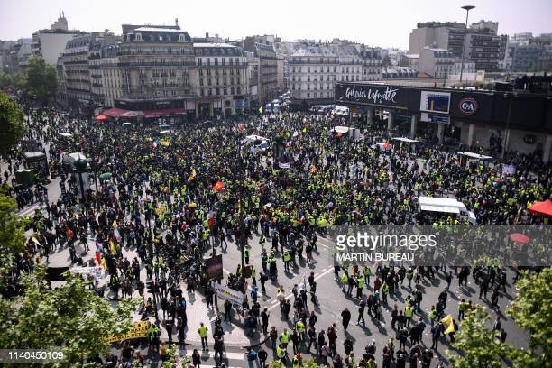 People including some wearing a yellow vest gather in front of the Montparnasse Tower prior to the start of May Day demonstrations in Paris on May 1...