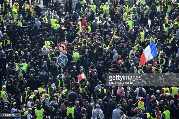 TOPSHOT People including some wearing a yellow vest gather in front of the Montparnasse Tower prior to the start of May Day demonstrations in Paris...
