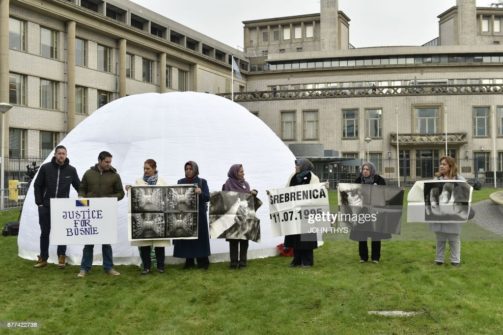 People, including victims, protest in front of the International Criminal Tribunal for the former Yugoslavia (ICTY) in The Hague, on November 22, 2017, during the verdict in the genocide trial of former Bosnian Serbian commander Ratko Mladic. Dubbed 'The Butcher of Bosnia,' Mladic on November 22, 2017 sentenced to life for Bosnia genocide in the brutal 1990s Balkans conflicts. THYS