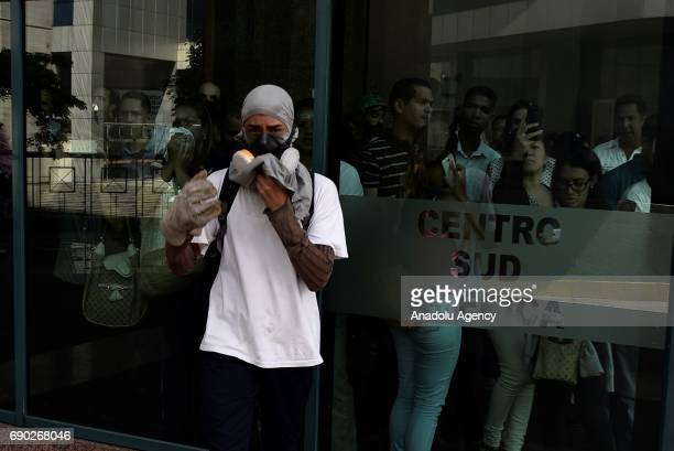 People inside a bank use their mobile phones to film protestors during clashes in a protest against President Nicolas Maduro's government in Caracas...