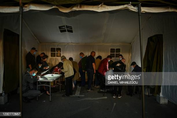 "People inside a tent use mobile phones' light to fill-in forms prior being vaccinated during the vaccination marathon organized at the ""Bran Castle""..."