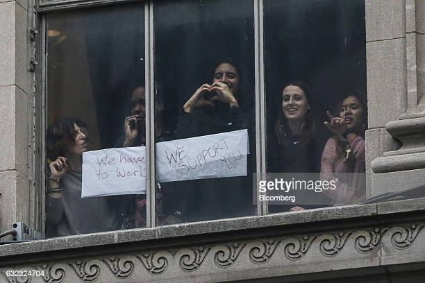 People inside an office building watch as demonstrators march towards Trump Tower during the Women's March in New York US on Saturday Jan 21 2017...