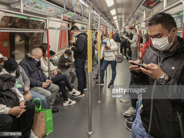 people inside subway cover their faces with masks during the coronavirus covid19 health crisis in hong kong - public transportation stock pictures, royalty-free photos & images