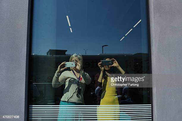 People inside the Brooks Building, Manchester Metropolitan University photograph the departure of labour leader Ed Miliband after a speech on the...