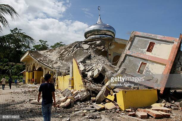 People inspect a damaged building in the quakedevastated area after an earthquake measuring 64 on the Richter Scale rocked Pidie Jaya Aceh Indonesia...