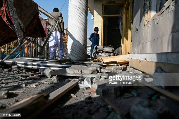 People inspect a damaged house after several rockets land at Khair Khana, north west of Kabul on November 21, 2020. - A series of loud explosions...