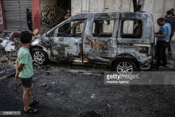 People inspect a damaged vehicle after Israeli army carried out airstrike over a building in Sheikh Ridvan neighbourhood in Gaza City, Gaza on May...