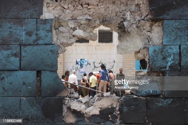 People inspect a damaged wall of a police station after a car bomb attack, which was happened as conscripts were gathering for morning assembly, in...