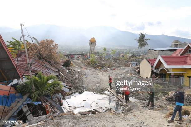 People inspect a destroyed mosque, which was dragged 300 metres due to an earthquake measuring 7.7 SR and the tsunami wave, in Palu, Central...