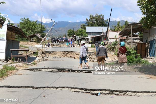 People inspect a destroyed road, connects two villages namely Petobo and Balaroa, due to an earthquake measuring 7.7 SR and the tsunami wave, in...