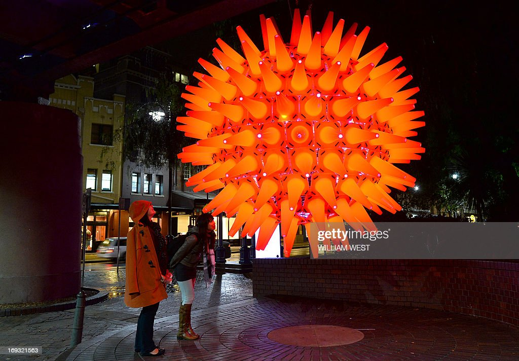 People inspect a light installation as landmarks around the city beaome part of Vivid Sydney, the annual festival of light, music and ideas, on May 23, 2013. More than 60 interactive and immersive light sculptures and installations across Circular Quay, The Rocks, Walsh Bay, Darling Harbour and North Sydney took part in the festival. City skyscrapers will light up along with 3D mapped projections on Customs House, Museum of Contemporary Art Australia, and Cadman's Cottage. AFP PHOTO / William WEST