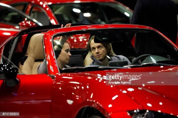 People inspect a vehicle during the Dubai International Motor Show 2017 at Dubai World Trade Centre in Dubai United Arab Emirates on November 14 2017