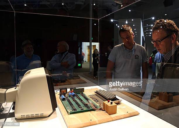 People inspect an Apple-1 computer, built in 1976, that is displayed during the First Bytes: Iconic Technology From the Twentieth Century, an online...
