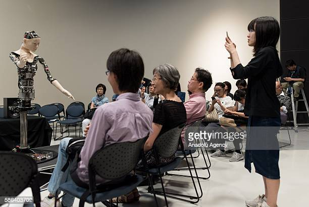 People inspect and take a photo of the humanoid robot called Alter designed by scientists in Japan during the exhibition at the National Museum of...