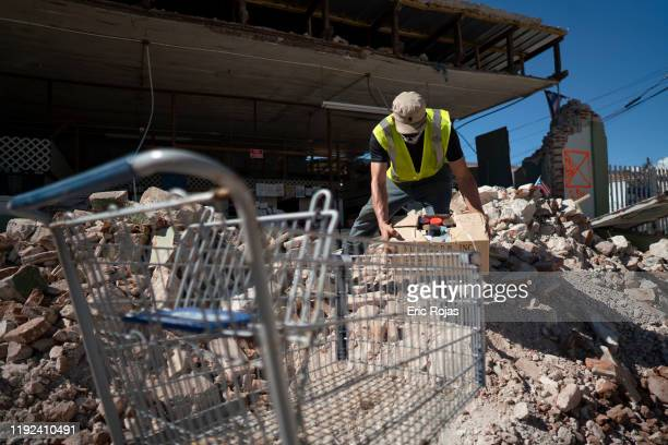 People inspect damage and help to take merchandise out of a local store after a 64 earthquake hit just south of the island on January 7 2020 in...