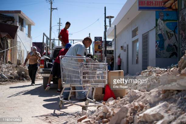 People inspect damage and help to take merchandise out of a local store after a 6.4 earthquake hit just south of the island on January 7, 2020 in...
