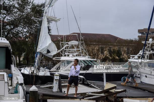 People inspect damage at a Marina from Hurricane Sally in downtown Pensacola Florida on September 16 2020 Hurricane Sally barrelled into the US Gulf...