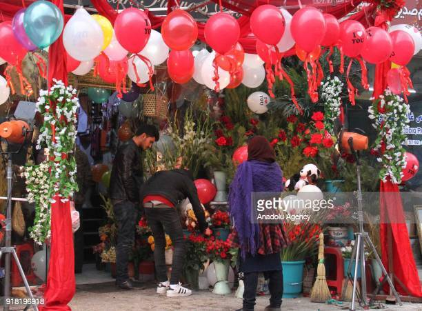 People inspect flowers at a decorated souvenir shop on Valentine's Day in Kabul Afghanistan on February 14 2018