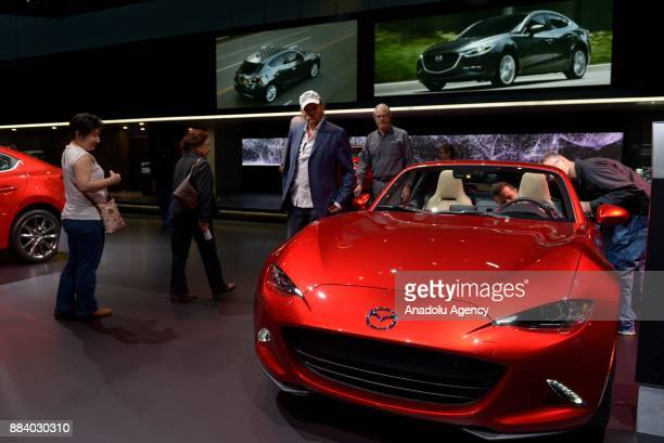 People inspect the 2018 Mazda MX5 Miata on display at the Los Angeles Auto Show in the Los Angeles Convention Center in Los Angeles California on...